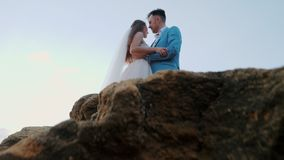 Όμορφο νέο γαμήλιο ζεύγος που στέκεται στην ακροθαλασσιά με τους βράχους Το Newlyweds ξοδεύει το χρόνο μαζί: αγκαλιάστε, φιλήστε  απόθεμα βίντεο