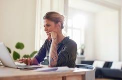 Όμορφο νέο γραφείο συνεδρίασης γυναικών στο σπίτι που χρησιμοποιεί το lap-top Στοκ Εικόνες