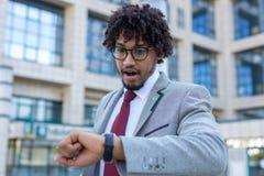 Όμορφο νέο επιχειρησιακό άτομο αργά για την εργασία που εξετάζει το ρολόι του που συγκλονίζεται στοκ εικόνες