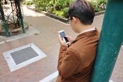Όμορφο νέο επιχειρησιακό άτομο που φαίνεται κινητό τηλέφωνο στο χέρι του κλίνοντας έναν πόλο σε υπαίθριο Στοκ φωτογραφίες με δικαίωμα ελεύθερης χρήσης
