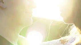 Όμορφο νέο ερωτευμένο φιλί ζεύγους σε έναν τομέα στο ηλιοβασίλεμα απόθεμα βίντεο