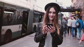 Όμορφο νέο ευτυχές ευρωπαϊκό κορίτσι στο μοντέρνο καπέλο που περπατά κατά μήκος της πολυάσχολης οδού πόλεων που χρησιμοποιεί το s απόθεμα βίντεο
