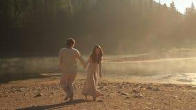 Όμορφο νέο ζεύγος ερωτευμένο στα παραδοσιακά ουκρανικά ενδύματα που χορεύουν κοντά στη λίμνη Synevir βουνών στο χρυσό φιλμ μικρού μήκους