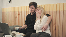 Όμορφο νέο ζεύγος με το lap-top στον καφέ, προσέχουν τον κινηματογράφο και πίνουν τον καφέ από κοινού Στοκ Φωτογραφίες