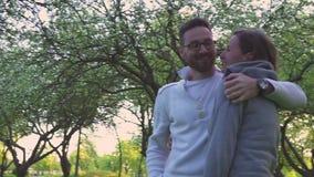 Όμορφο νέο ζεύγος που αγκαλιάζει και που φιλά στο πάρκο απόθεμα βίντεο