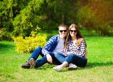 Όμορφο νέο ζεύγος που αγκαλιάζει στα γυαλιά ηλίου με το υπόβαθρο φύσης στοκ φωτογραφία