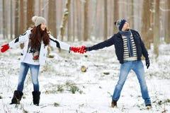 Όμορφο νέο ζεύγος που περπατά στο χιονώδες χειμερινό δάσος Στοκ Εικόνα