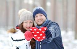 Όμορφο νέο ζεύγος που περπατά στο χιονώδες χειμερινό δάσος Στοκ Φωτογραφία