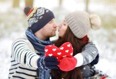 Όμορφο νέο ζεύγος που περπατά στο χιονώδες χειμερινό δάσος Στοκ Εικόνες