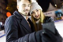 Όμορφο νέο ζεύγος που χρησιμοποιεί αυτοί κινητό τηλέφωνο στο skatin πάγου Στοκ φωτογραφία με δικαίωμα ελεύθερης χρήσης