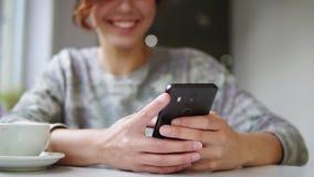 Όμορφο νέο θηλυκό που χρησιμοποιεί το κινητό τηλέφωνό της στον καφέ και χαμογελώντας Γυναίκα που χρησιμοποιεί app στο smartphone  απόθεμα βίντεο