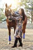Όμορφο νέο θηλυκό που περπατά και που χαϊδεύει το καφετί άλογό της σε μια επαρχία Στοκ εικόνες με δικαίωμα ελεύθερης χρήσης