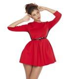 Όμορφο νέο θηλυκό στην κόκκινη μόνιμη τοποθέτηση φορεμάτων Στοκ Εικόνα