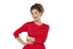 Όμορφο νέο θηλυκό στην κόκκινη μόνιμη τοποθέτηση φορεμάτων Στοκ φωτογραφία με δικαίωμα ελεύθερης χρήσης