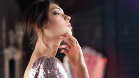 Όμορφο νέο ισπανικό κορίτσι πλάγιας όψης που απολαμβάνεται το καθαρό δέρμα σχετικά με το πρόσωπο με το χέρι απόθεμα βίντεο