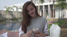 Όμορφο νέο κακάο ποτών γυναικών κατά τη διάρκεια του προγεύματος πρωινού στη βίλα πολυτέλειας Θηλυκό που πίνει την καυτή σοκολάτα απόθεμα βίντεο