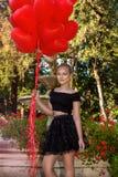 Όμορφο νέο κορίτσι βαλεντίνων με το κόκκινο γέλιο μπαλονιών, στο πάρκο Όμορφο ευτυχές παιδί Γιορτή Χριστουγέννων Χαρούμενος λίγο  στοκ φωτογραφίες με δικαίωμα ελεύθερης χρήσης