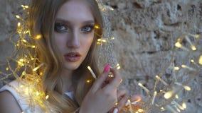 Όμορφο νέο κορίτσι ενάντια στον τοίχο, το κορίτσι που κρατά μια γιρλάντα, φω'τα Χριστουγέννων απόθεμα βίντεο