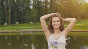 Όμορφο νέο κορίτσι με μακρυμάλλη σε μια τοποθέτηση θερινών φορεμάτων στη κάμερα σε ένα υπόβαθρο μιας λίμνης στο πάρκο Πάπιες φιλμ μικρού μήκους