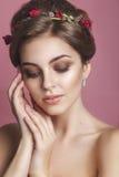 Όμορφο νέο κορίτσι με μια floral διακόσμηση στην τρίχα της όμορφο πρόσωπο αυτή σχετι&ka Νεολαία και έννοια φροντίδας δέρματος Στοκ Φωτογραφίες