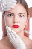Όμορφο νέο κορίτσι με τα κόκκινα χείλια που παίρνουν την καλλυντική έγχυση στο μέτωπο Απομονωμένος στο γκρι στοκ εικόνα