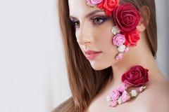 Όμορφο νέο κορίτσι με τα λουλούδια applique στο πρόσωπο Στοκ Εικόνα