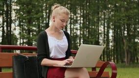 Όμορφο νέο κορίτσι με τα ξανθά μαλλιά σε έναν πάγκο πάρκων που λειτουργεί στο lap-top της Κορίτσι που χρησιμοποιεί το lap-top, δα φιλμ μικρού μήκους