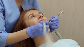 Όμορφο νέο κορίτσι με την παραλαβή στο κορίτσι οδοντιάτρων στον οδοντίατρο απόθεμα βίντεο