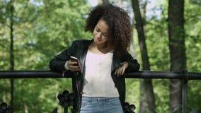 Όμορφο νέο κορίτσι με τη σκοτεινή σγουρή τρίχα που χρησιμοποιεί το τηλέφωνο κυττάρων της, υπαίθριο