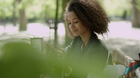 Όμορφο νέο κορίτσι με τη σκοτεινή σγουρή τρίχα που χρησιμοποιεί το τηλέφωνο κυττάρων της, υπαίθριο απόθεμα βίντεο