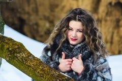 Όμορφο νέο κορίτσι με τις κουρτίνες το χειμώνα στο γκρίζο παλτό στοκ εικόνες