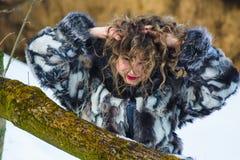 Όμορφο νέο κορίτσι με τις κουρτίνες το χειμώνα στο γκρίζο παλτό στοκ φωτογραφία