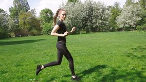 Όμορφο νέο κορίτσι με τις μακριές πλεξούδες που τρέχουν γύρω στο πάρκο, υγιής τρόπος ζωής Ευρωπαϊκά τραίνα γυναικών στο πάρκο φιλμ μικρού μήκους
