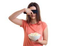 Όμορφο νέο κορίτσι με τον τηλεχειρισμό TV και pop-corn στα χέρια Στοκ φωτογραφία με δικαίωμα ελεύθερης χρήσης