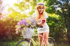 Όμορφο νέο κορίτσι με το εκλεκτής ποιότητας ποδήλατο και λουλούδια στο υπόβαθρο πόλεων στο φως του ήλιου υπαίθριο Στοκ Φωτογραφία