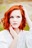 Όμορφο νέο κορίτσι με το κόκκινο τρίχωμα Στοκ Εικόνες