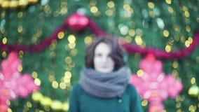 Όμορφο νέο κορίτσι με το μεγάλο μαντίλι που χαμογελά υπαίθρια το χειμώνα, ελαφρύ υπόβαθρο Χριστουγέννων Υπαίθριο χειμερινό πορτρέ φιλμ μικρού μήκους