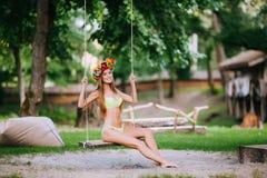 Όμορφο νέο κορίτσι με το όμορφο χαμόγελο σε μια ταλάντευση τη θερινή ημέρα υπαίθρια Στοκ Φωτογραφία