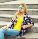 Όμορφο νέο κορίτσι μόδας που φορά ένα ελεγμένο πουκάμισο και τα γυαλιά ηλίου Στοκ Φωτογραφίες