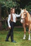 Όμορφο νέο κορίτσι πορτρέτου στο άσπρο πουκάμισο και μαύρα εσώρουχα με το μακρυμάλλες επόμενο άλογο ομορφιάς στο δασικό μοντέρνο  στοκ εικόνες