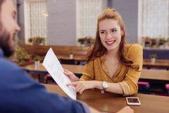Όμορφο νέο κορίτσι που δείχνει τα έγγραφα και που εξετάζει τον μπάρμαν στοκ εικόνες με δικαίωμα ελεύθερης χρήσης