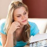 Όμορφο νέο κορίτσι που διαβάζει ένα καιρικό βιβλίο Στοκ Φωτογραφία