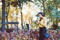 Όμορφο νέο κορίτσι που ελέγχει και που στέλνει ένα μήνυμα κειμένου στο τηλέφωνό της Στοκ Φωτογραφία
