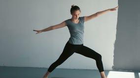 Όμορφο νέο κορίτσι που κάνει την άσκηση γιόγκας θηλυκά τεντώματα πριν από τα όπλα και τα πόδια ενός γιόγκας κατηγορίας τεντώματος απόθεμα βίντεο
