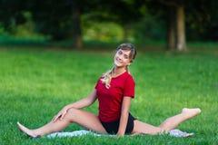 Όμορφο νέο κορίτσι που κάνει τις διασπασμένες ασκήσεις Στοκ Εικόνες