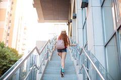 Όμορφο νέο κορίτσι που περπατά από τα βήματα σε ένα υπόβαθρο πόλεων Στοκ φωτογραφία με δικαίωμα ελεύθερης χρήσης
