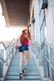 Όμορφο νέο κορίτσι που περπατά από τα βήματα σε ένα υπόβαθρο πόλεων Στοκ Φωτογραφία