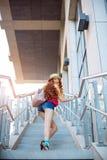 Όμορφο νέο κορίτσι που περπατά από τα βήματα σε ένα υπόβαθρο πόλεων Στοκ εικόνες με δικαίωμα ελεύθερης χρήσης