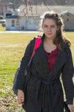 Όμορφο νέο κορίτσι που προέρχεται κατ' οίκον από το σχολείο με την τσάντα βιβλίων στον ώμο Στοκ Εικόνα