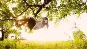 Όμορφο νέο κορίτσι που ταλαντεύεται στην ταλάντευση κοντά σε μια βαλανιδιά και που γελά στη ρύθμιση του ήλιου Ξένοιαστη ψυχαγωγία απόθεμα βίντεο